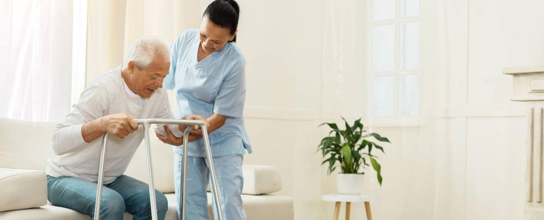 caregiver assisting senior man in his walker