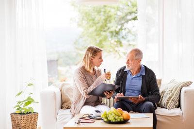 caregiver reminding senior man about medicine