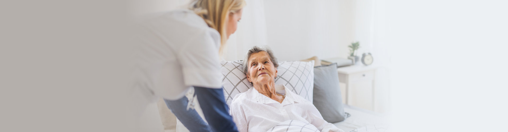 caregiver putting senior woman in bed