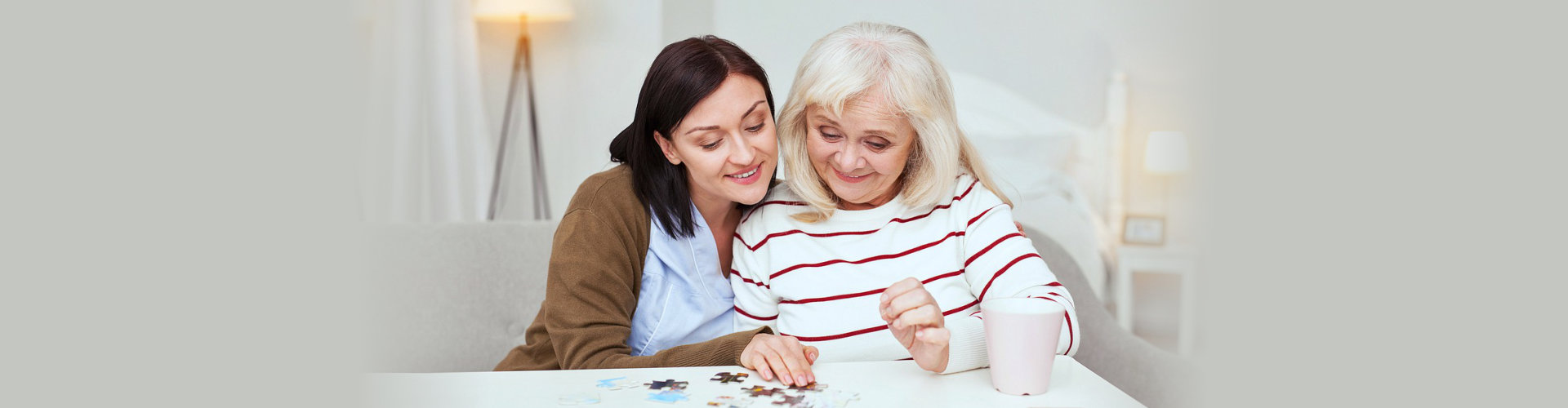 caregiver and senior woman solving the puzzle