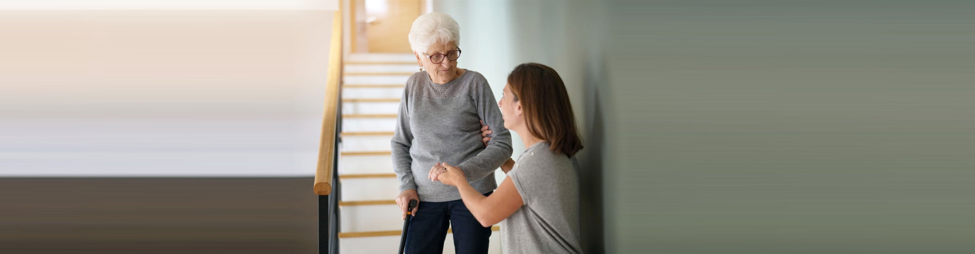 caregiver assisting senior woman going down on the stairs
